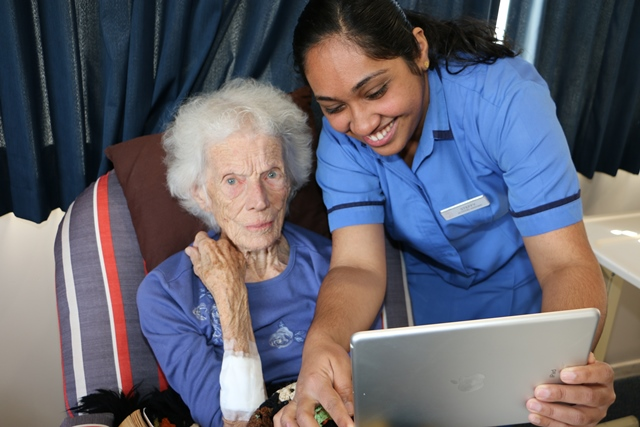 Older person and caregiver using tablet